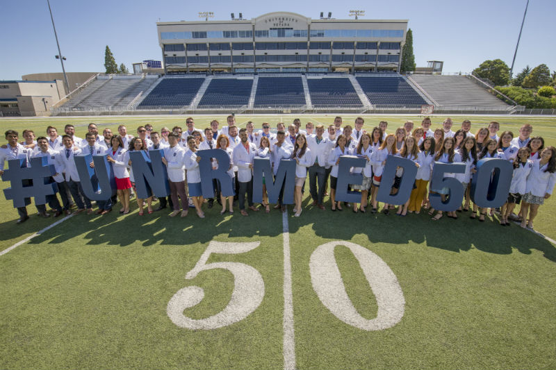 UNR Med Class of 2020 students on the 50-yard line at Mackay Stadium