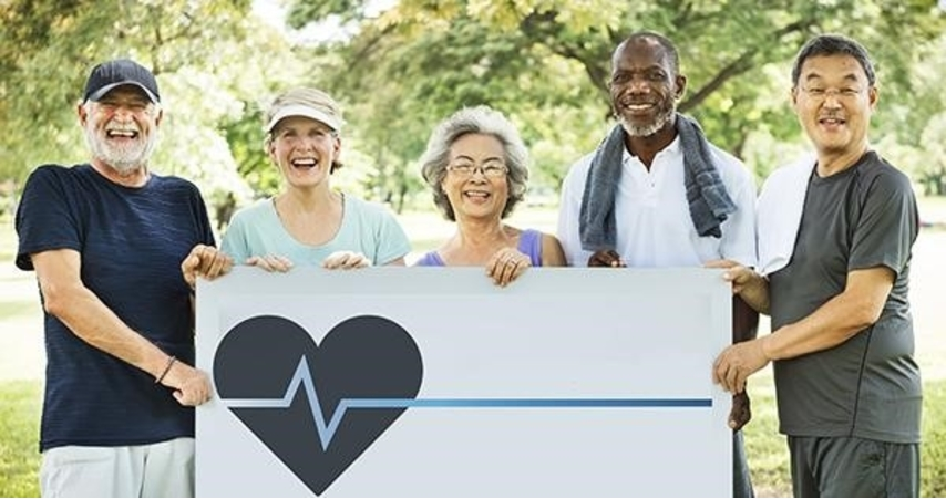 Photo of people holding a sign with a heart and EKG symbol on it