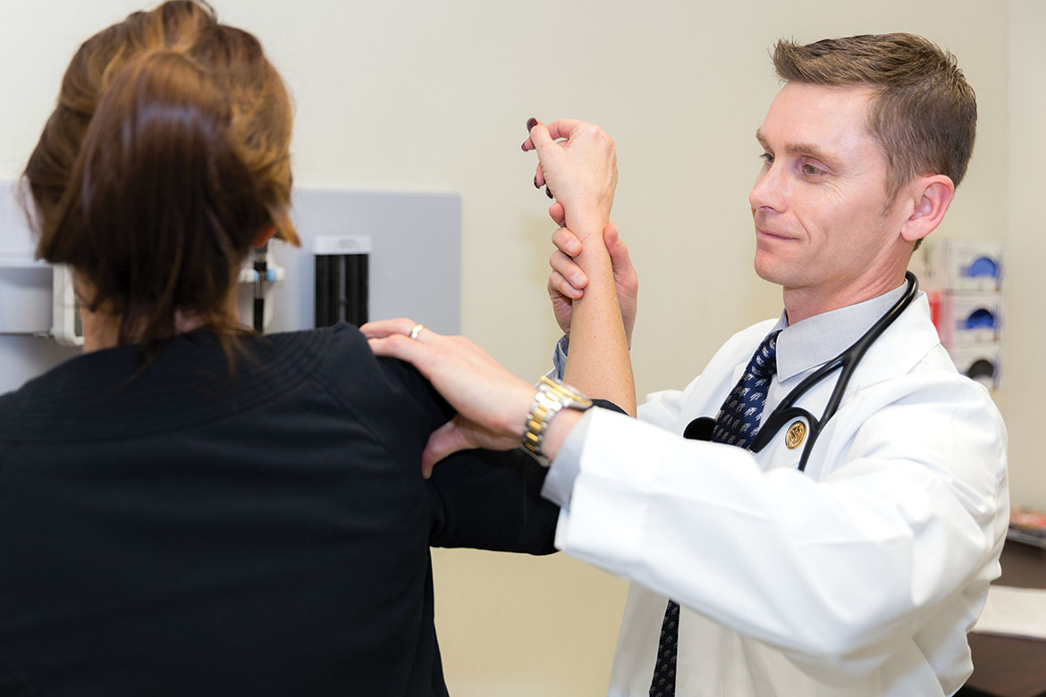 Brian Lauf examines a patient's shoulder