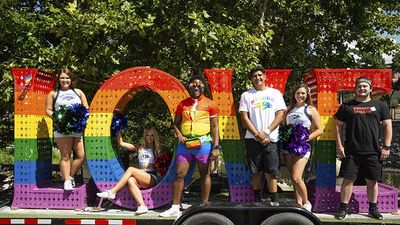 """A group of people, including two Nevada cheerleaders and some wearing University of Nevada, shirts, stand inside of and next to giant letters """"LOVE"""" that are painted with the LGBTQ+ rainbow of colors, red, yellow, purple, green and indigo."""